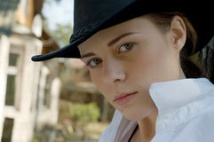 Woman-cowboy. Portrait of a woman in a white shirt and cowboy hat on a ranch Royalty Free Stock Photo