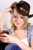Woman cowboy with bottle of whiskey Royalty Free Stock Photos