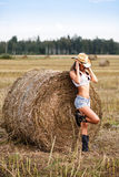 Woman in cowboy hat near a straw bale Royalty Free Stock Images