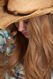 Woman cowboy hat plaid close face partly hidden. A woman with her cowgirl hat on with her head looking down Stock Photo