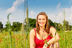 Woman cowering in meadow of field Stock Image