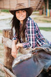 Woman cowgirl leaning on fence in village and looking away Stock Photos