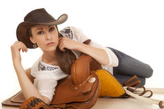Woman cowgirl white blouse laying on a saddle Stock Photos