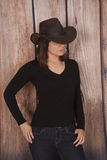 Woman cowgirl wooden wall eyes hid Stock Photo
