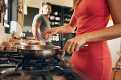 Woman cracking an egg into a frying pan Royalty Free Stock Images