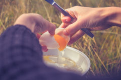 Woman cracking an egg on portable camping stove Stock Photo
