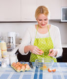 Woman cracking eggs into bowl Royalty Free Stock Photo