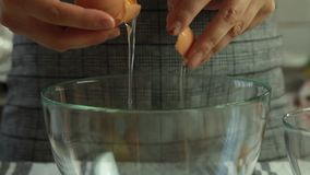 Woman cracking eggs for cooking chocolate mousse with orange jelly dessert. On table in the kitchen closeup stock footage