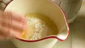 Woman cracking eggs into a jug of flour stock footage