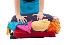 Woman crammed full of clothes in red suitcase Royalty Free Stock Photos