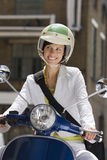 Woman in crash helmet riding on scooter in street, making sideways glance, smiling, front view Royalty Free Stock Images