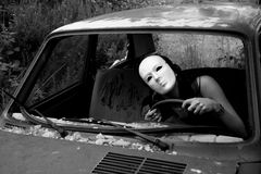 A woman in a crashed car. A masked woman in a crashed car stock image