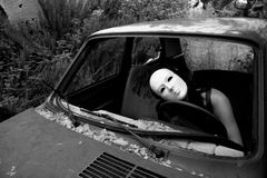 A woman in a crashed car. A masked woman in a crashed car Stock Photos