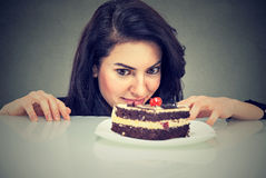 Woman craving cake dessert, eager to eat sweet food. Woman craving cake dessert, eager to eat, isolated on gray background stock images