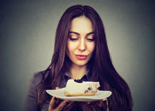 Woman craving cake dessert, eager to eat. Young woman craving cake dessert, eager to eat stock images