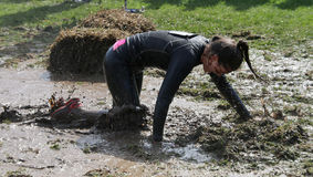 Woman crawling on her knees through the mud Stock Images
