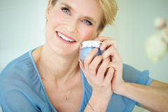 Woman With Cream. Beautiful smiling elegant woman indoors wearing blue blouse and short blond hair holding a cream jar. Skincare concept over forty Stock Photography