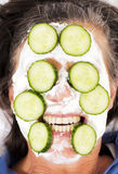 Woman with cream and cucumbers on her face Royalty Free Stock Photo