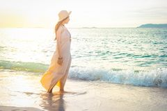 Woman in a cream dress is walking on the beautiful beach at suns Stock Images