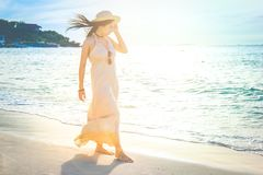 Woman in a cream dress is walking, enjoying the beautiful sunset Stock Images