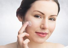 Woman with cream on face against white wall Stock Photos