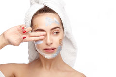 Woman with cream on face covering eye Stock Photo