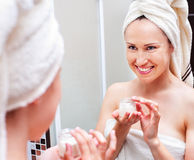 Woman with cream looking at mirror Royalty Free Stock Image