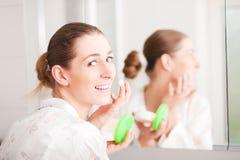 Woman creaming face Stock Photo