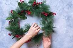 Woman Creates Green Christmas Decorative Wreath stock photography