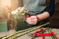 Woman creating decorative bouquet of flowers. Royalty Free Stock Photography