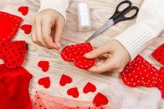 Woman creating red heart on wooden table. gift for St. Valentine`s Day handmade Stock Image