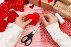 Woman creating red heart on wooden table. gift for St. Valentine`s Day handmade Royalty Free Stock Images