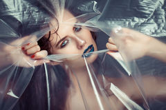 Woman with creative eye makeup peering cellophane Stock Images