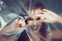 Woman with creative eye makeup peering cellophane Royalty Free Stock Image