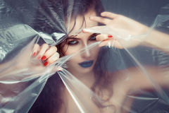 Woman with creative eye makeup peering cellophane Royalty Free Stock Images
