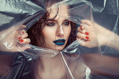 Woman with creative eye makeup peering cellophane Royalty Free Stock Photo