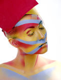 Woman with creative geometry make up, red, yellow, blue closeup smiling colored, bright concept Royalty Free Stock Photo
