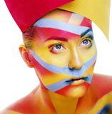 Woman with creative geometry make up, red, yellow, blue closeup. Smiling colored, bright creative concept royalty free stock image