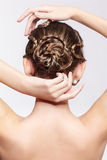 Woman with creative hairdo. Back view portrait of beautiful young dark blonde woman with creative plait hairdo on gray Royalty Free Stock Image