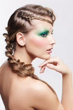 Woman with creative hairdo. Portrait of beautiful young dark blonde woman with creative plait hairdo and green eye shades make up stock image