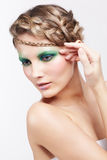 Woman with creative hairdo. Portrait of beautiful young dark blonde woman with creative braid hairdo and green eye shades make-up  posing on gray Stock Photos