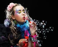 Woman with creative make-up blowing soap bubbles. Fashion model with creative make-up blowing soap bubbles. Doll style Stock Image