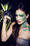 Woman with creative make up like snake with rat in her hands Stock Images