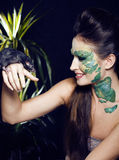Woman with creative make up like snake with rat in her hands Stock Image