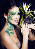 Woman with creative make up like snake with rat in her hands Stock Photography