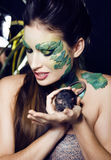 Woman with creative make up like snake with rat in her hands Royalty Free Stock Photos