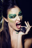 Woman with creative make up like snake with rat in her hands Stock Photos