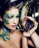 Woman with creative make up like snake with rat in her hands Stock Photo