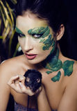 Woman with creative make up like snake and rat in her hands, halloween horror closeup Stock Photo