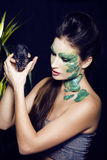 Woman with creative make up like snake and rat in Stock Image